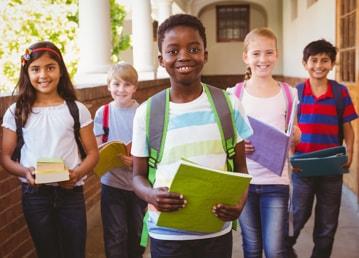 5 élèves souriants marchent dans le couloir d'une école avec leurs cahiers de notes en main et portant leur sac à dos