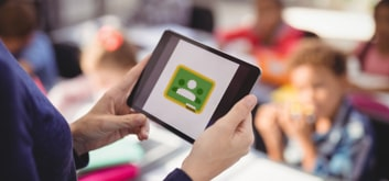 Teacher holding a tablet with the Google Classroom logo in front of her blurred classroom