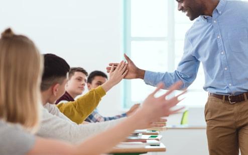 Profesor chocando los cinco con uno de sus alumnos de secundaria en el aula