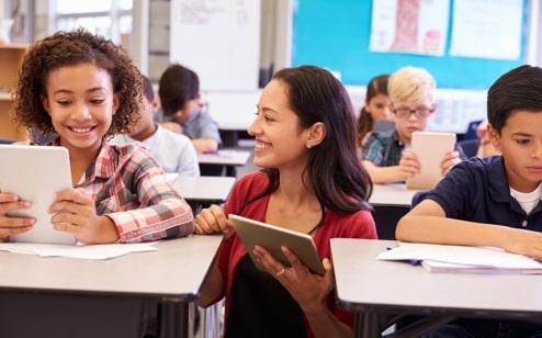 Profesora con su iPad sonriendo y explicando algo a un alumno sonriente