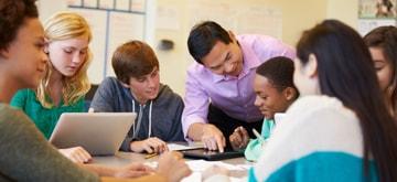 6 alumnos en una mesa redonda trabajando en una tarea en una tableta mientras su profesor les explica algo
