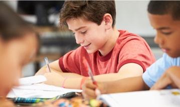 Twee studenten die op hun notitieboekjes schrijven