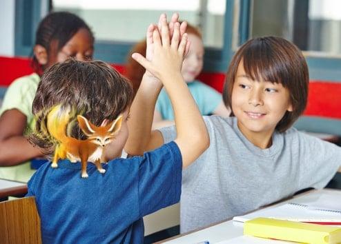 """Un élève avec une illustration de caméléon sur son épaule fait un """"tope là"""" à un autre élève souriant"""