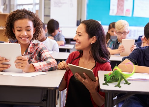 Teacher with her iPad smiling and explaining something to a smiling student