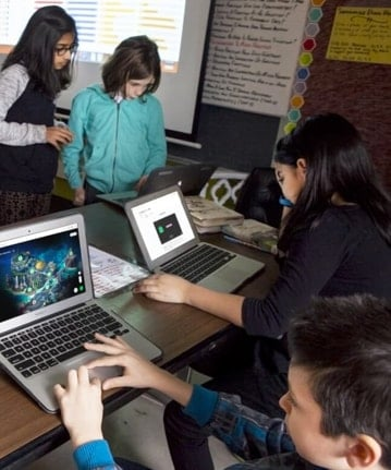 Two students using Classcraft Quests on their computers and two other students working on the same computer