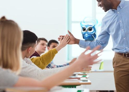 """Enseignant avec un hibou de Classcraft sur son bras fait un """"Tope là!"""" à un élève"""