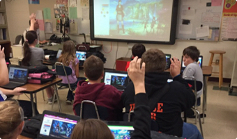 Group of students with their hands raised while Classcraft is shown on the smartboard